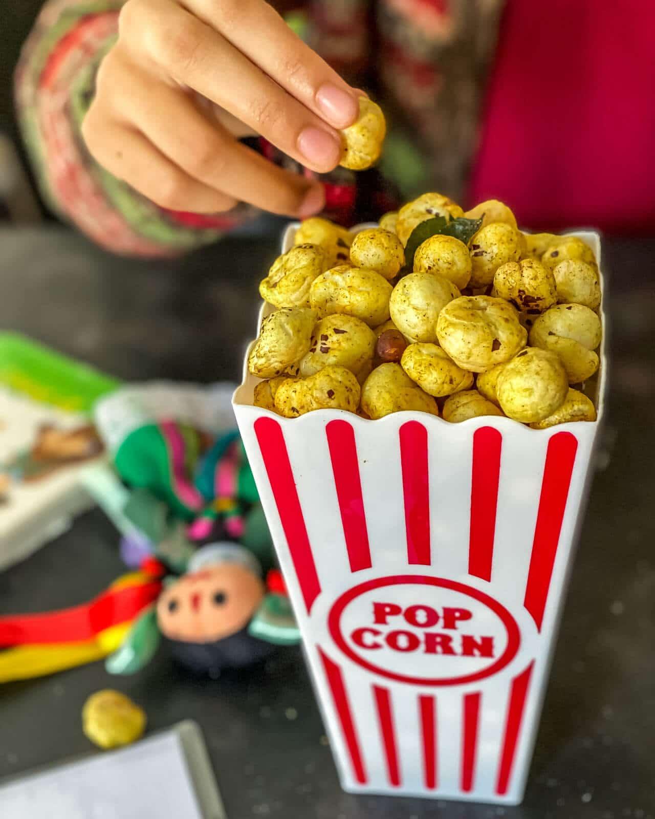 A hand picking a makhana kept in a popcorn box