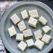 A light blue speckled plate with cubes of fresh cut paneer and a dish towel to the left with the words 20-minute homemade paneer at the top.