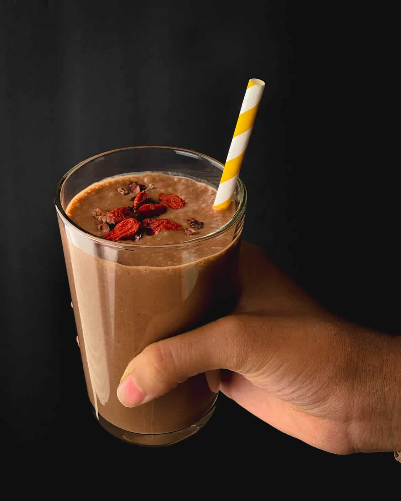 A hand holding a banana chocolate smoothie with goji berries on top and a yellow and white straw.