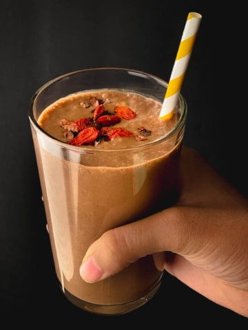 A hand holding a chocolate date smoothie in a clear glass cup with goji berries on the top of the smoothie and a yellow and white straw in the smoothie.