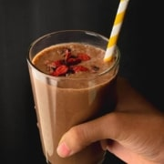 A hand holding a clear glass filled with chocolate smoothie, topped with goji berries, and a white and yellow straw sticking out with the words Chocolate Smoothie at the top in yellow.