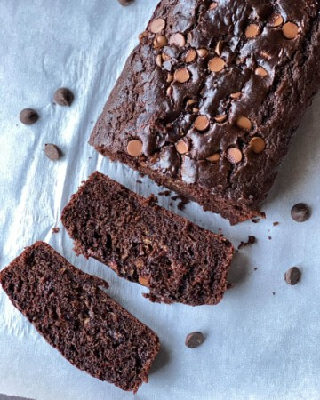 A loaf of double chocolate zucchini bread with two slices laying in front on a sheet of parchment paper.