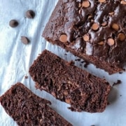 A loaf of chocolate zucchini bread sliced with two slices in the front on a sheet of parchment paper with the words chocolate zucchini bread at the top.