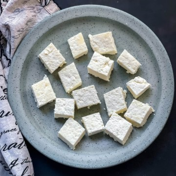 Cut cubes of paneer on a light blue speckled plate with a dish towel to the left.