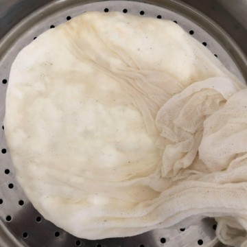 A cheesecloth on a colander gently squeezed to let go for excess whey.