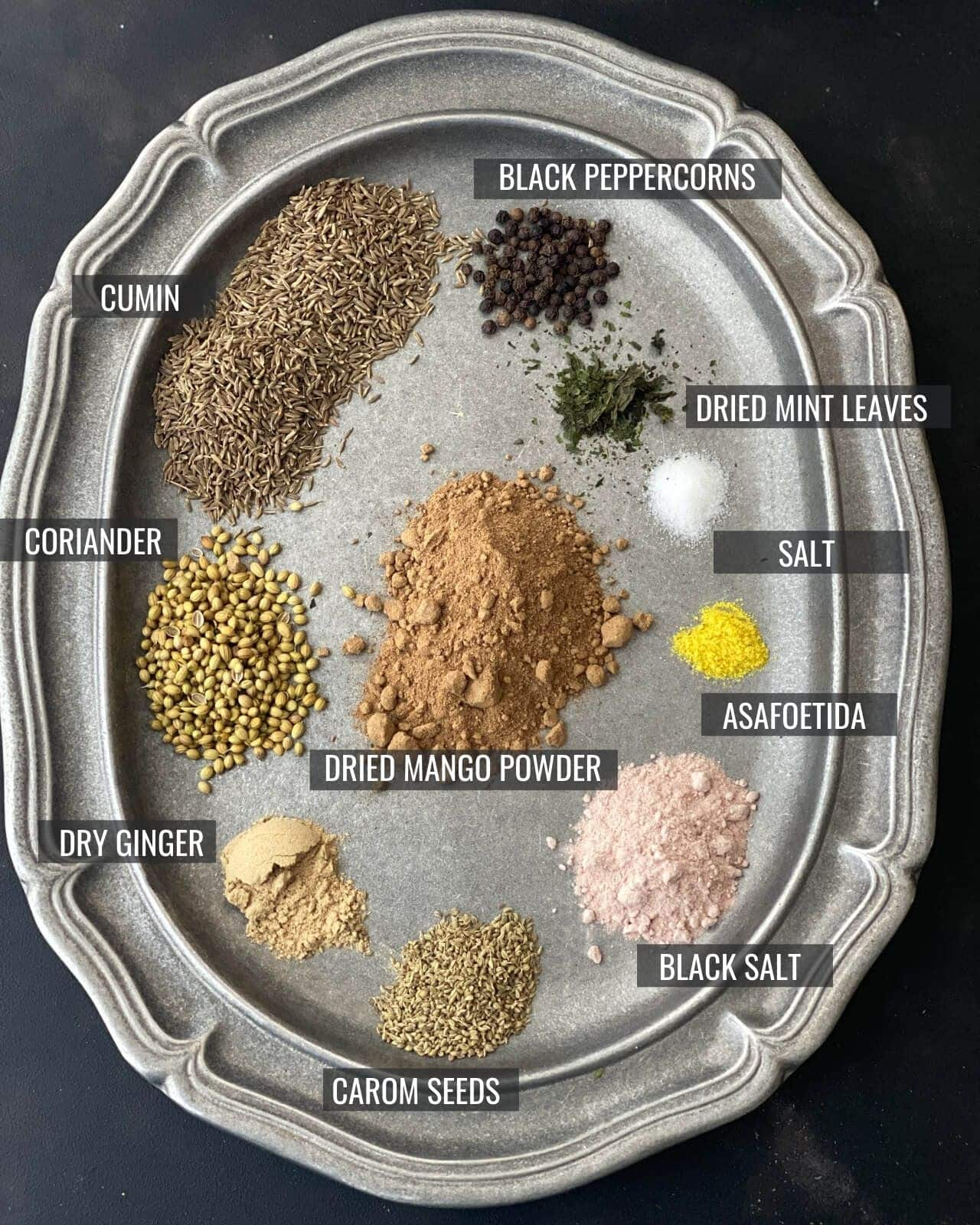 All 10 ingredients used in chaat masala laid out in a pewter plate