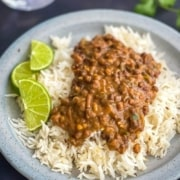 Lamgar ki dal served with cumin rice in a grey plate with 3 slices of lime on the side