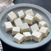 A light blue plate with chunks of fresh cut paneer with the words Instant Pot Homemade Paneer at the top.