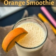 A large glass of orange smoothie with an orange wedge on the left side rim of the glass and the words orange smoothie in orange at the top.