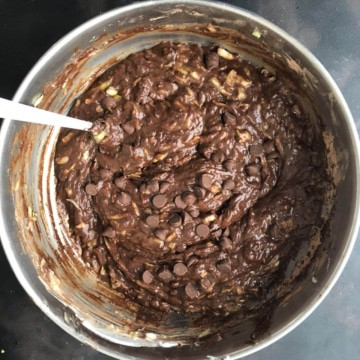 A silver mixing bowl with chocolate zucchini bread batter after adding the chocolate chips.