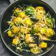 A black bowl with cheese topped steamed Brussel sprouts with the words Cheesy Brussel Sprouts at the bottom in yellow and a silver fork in the bowl.