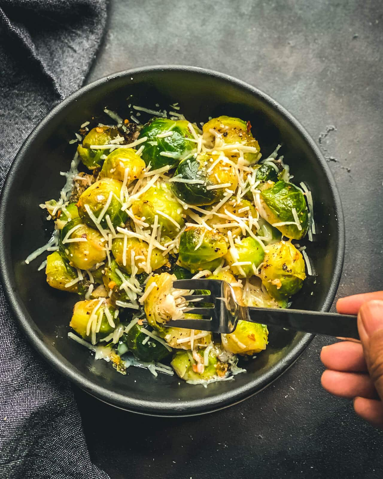 A black bowl of cheese topped steamed and sautéed Brussel sprouts with a silver fork poking into a Brussel sprout on a grey counter.