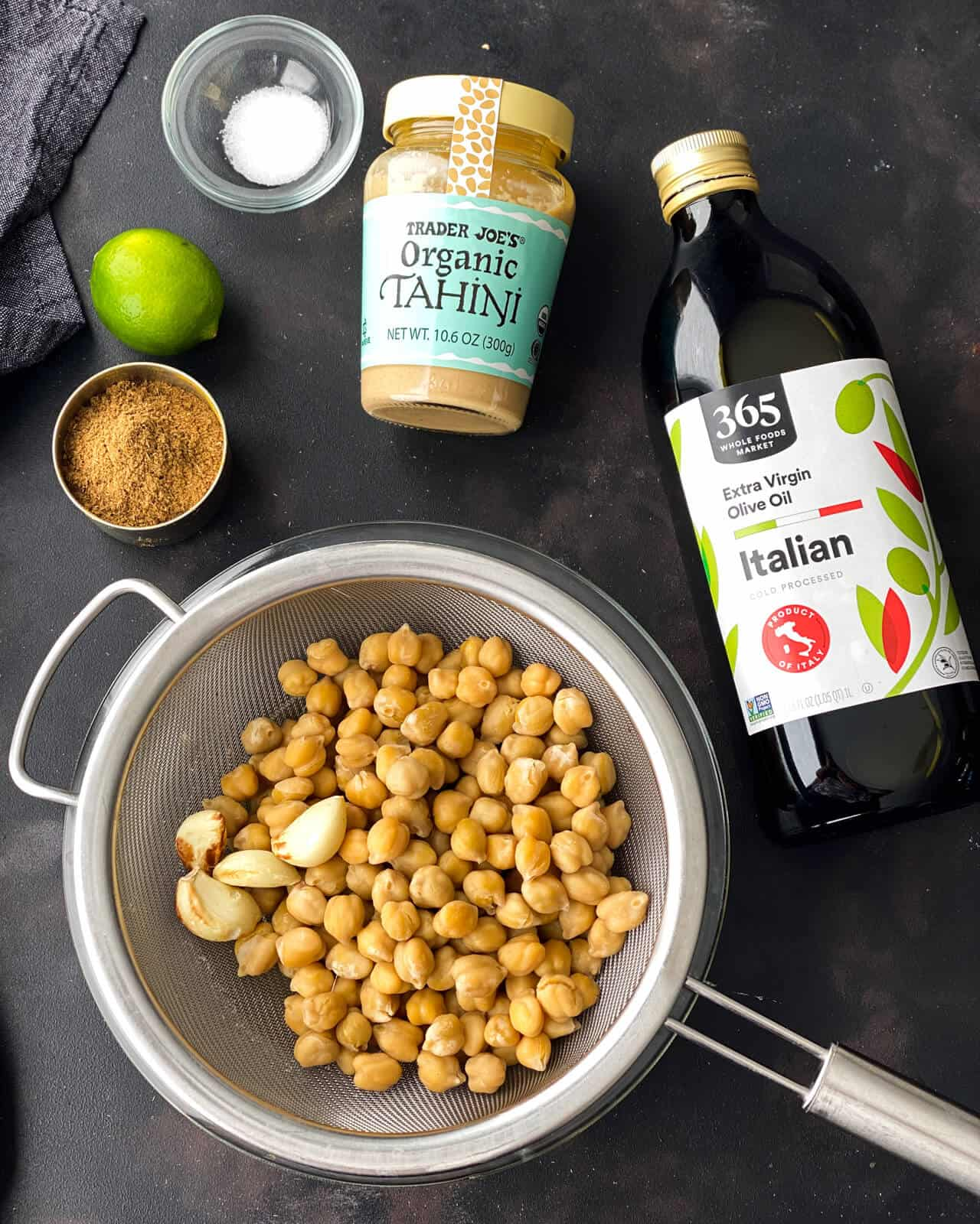 Chickpeas in a strainer with a bottle of olive oil, a jar of tahini, salt, a lime, and cumin above.