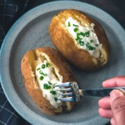 The words Instant Pot in the top right in white with the words baked potato below in yellow and a blue plate in the center with two baked potatoes topped with sour cream and chive and a hand holding a fork poking into one of the potatoes.