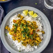 A grey plate with mung bean curry on top of rice and 3 wedges of lime on the plate.