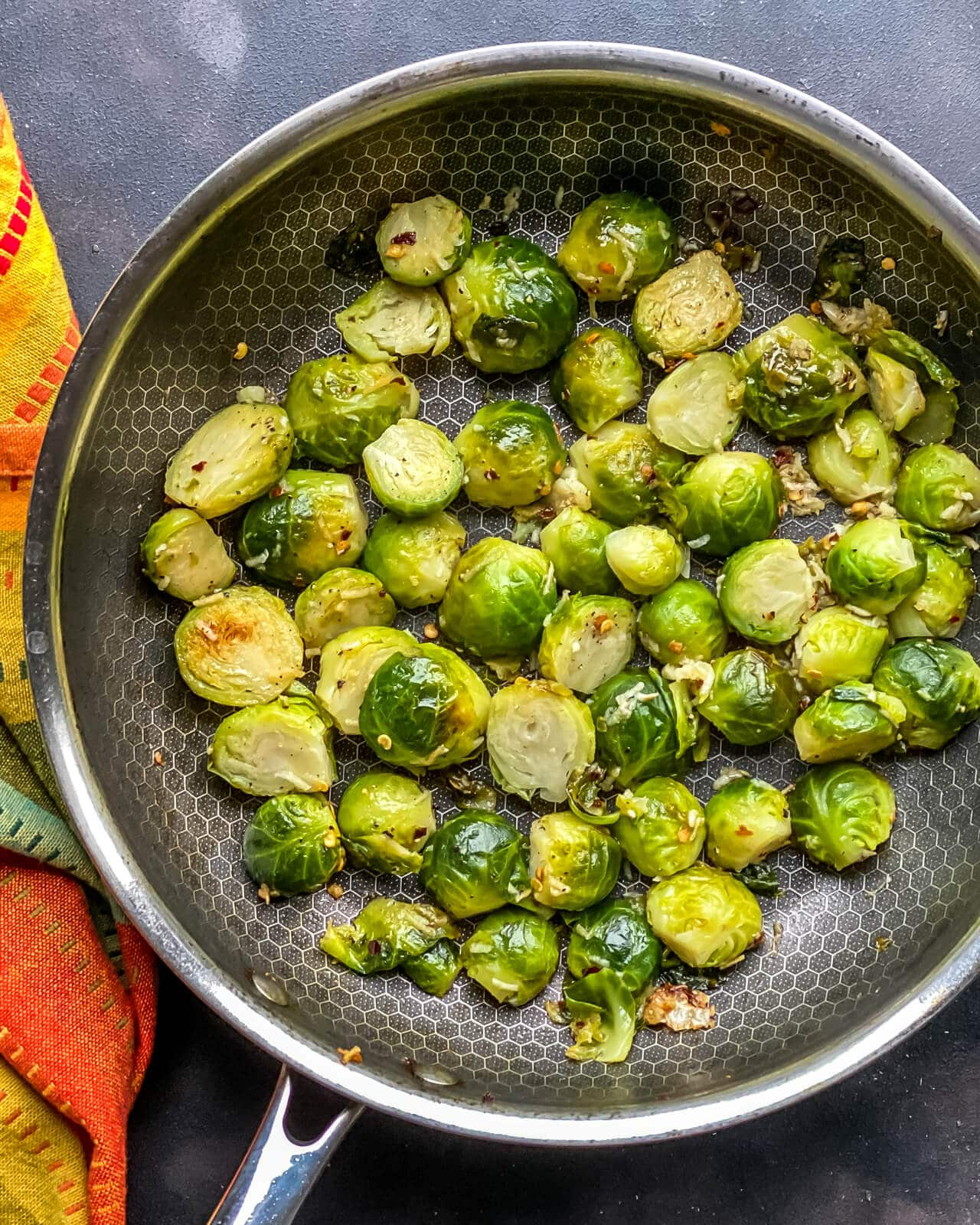 A silver pan of pan fried steamed Brussel sprouts on a grey counter with an orange and yellow towel to the left.