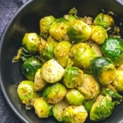 The words Steamed and Sautéed Brussel Sprouts at the top with a black bowl of bright green steamed and sautéed Brussel sprouts on a grey counter.