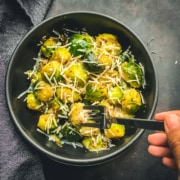 A black bowl with steamed and sautéed Brussel sprouts topped with cheese and a silver fork being poked into the bowl on a grey counter.