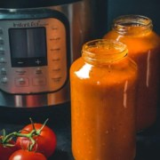 Two glass jars of pasta sauce in front of an instant pot with two tomatoes on the vine to the left with the words Instant Pot Classic Marinara Sauce at the top.