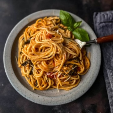 A light grey plate with a serving of instant pot spaghetti with a fork in the right side of the spaghetti pile and some basil at the top.