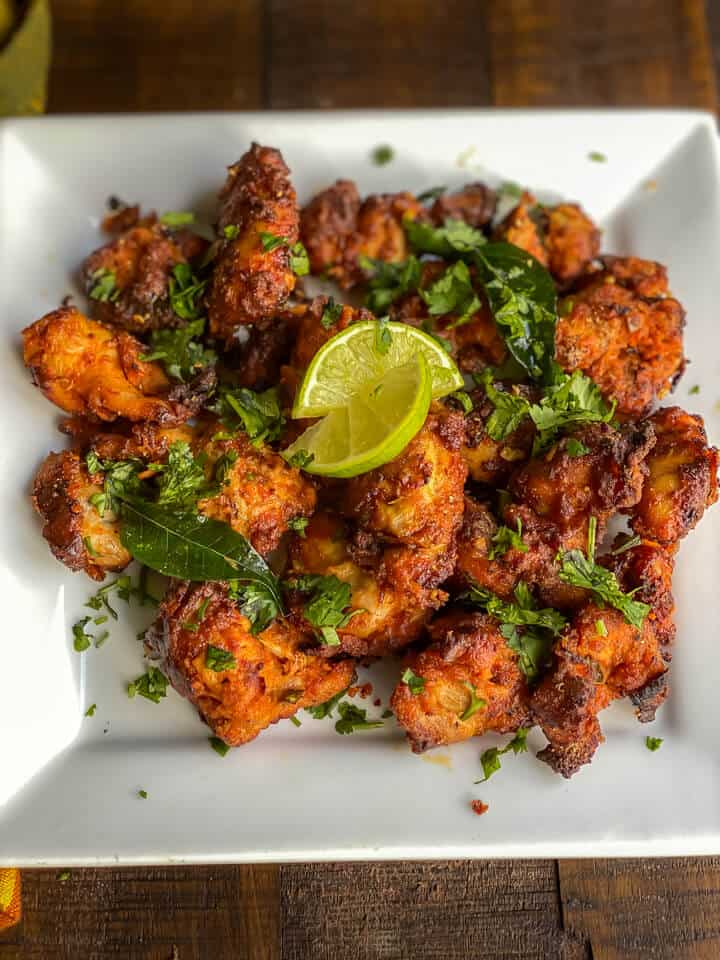 A white plate topped with chicken 65 pieces sprinkled with cilantro and lemon wedges.