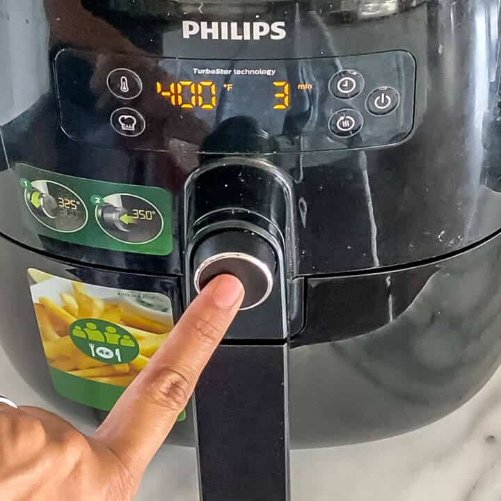 A hand pushing the preheat button on the air fryer at 400°F.