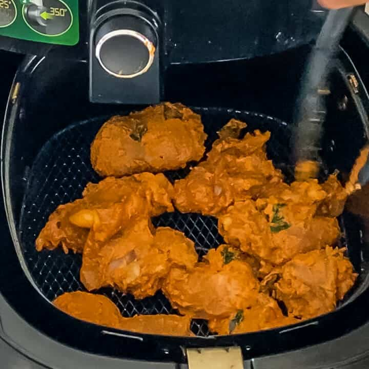 Chicken in the air fryer basket in a single layer.