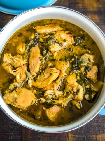A blue handled bowl with methi chicken on a wooden counter.