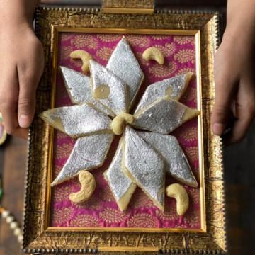 A hand holding a plate of Kaju barfi