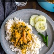 A light grey plate with a scoop of rice topped with methi chicken and a side of cucumbers on a wooden table with a grey towel to the left and the words Instant Pot Fenugreek Chicken at the top.