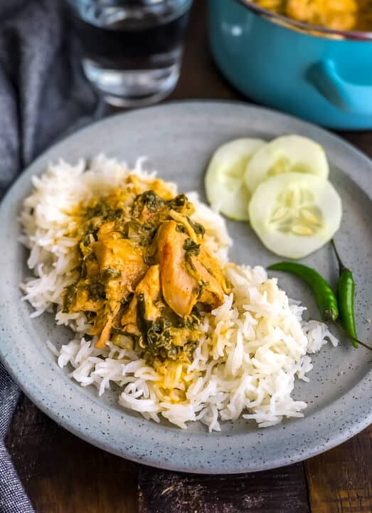 A light grey plate of methi murgh on rice with three cucumbers to the right on a wooden counter.