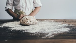 A photo by Annie Spratt, of a chef at a wooden counter with splattered flour and freshly kneaded dough. unsplash.com/photos/9DkKRpI9MsQ