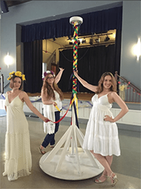 The three dancer encircle the maypole, which is braided with ribbons