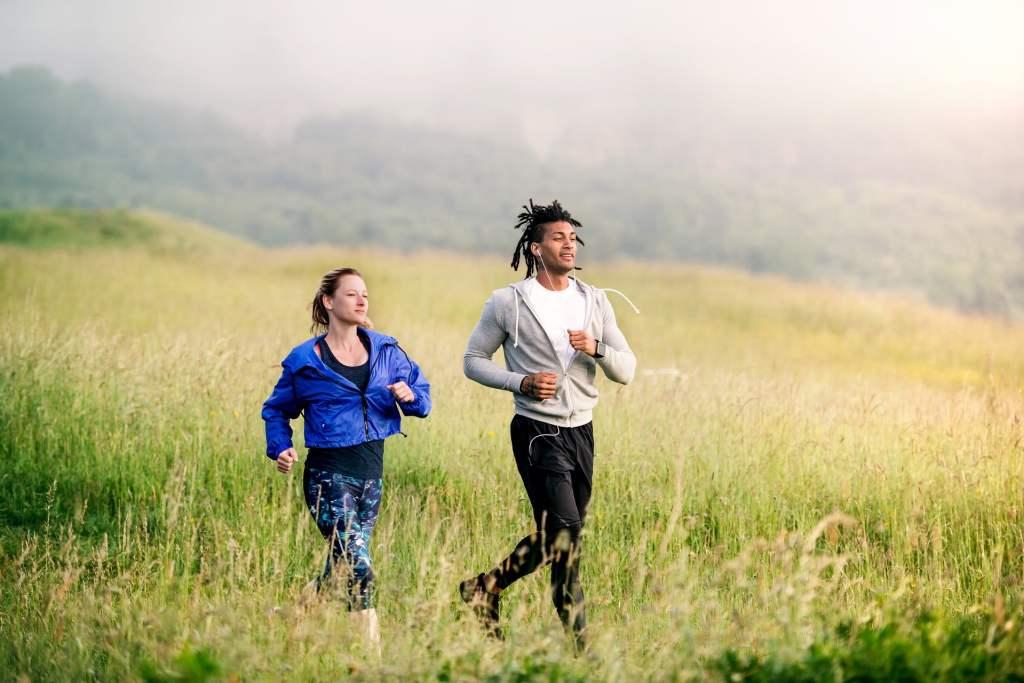 un ragazzo con i rasta e delle cuffie alle orecchie mentre ascolta musica sta correndo insieme ad una ragazza bionda in aperta campagna in un campo di erba verde