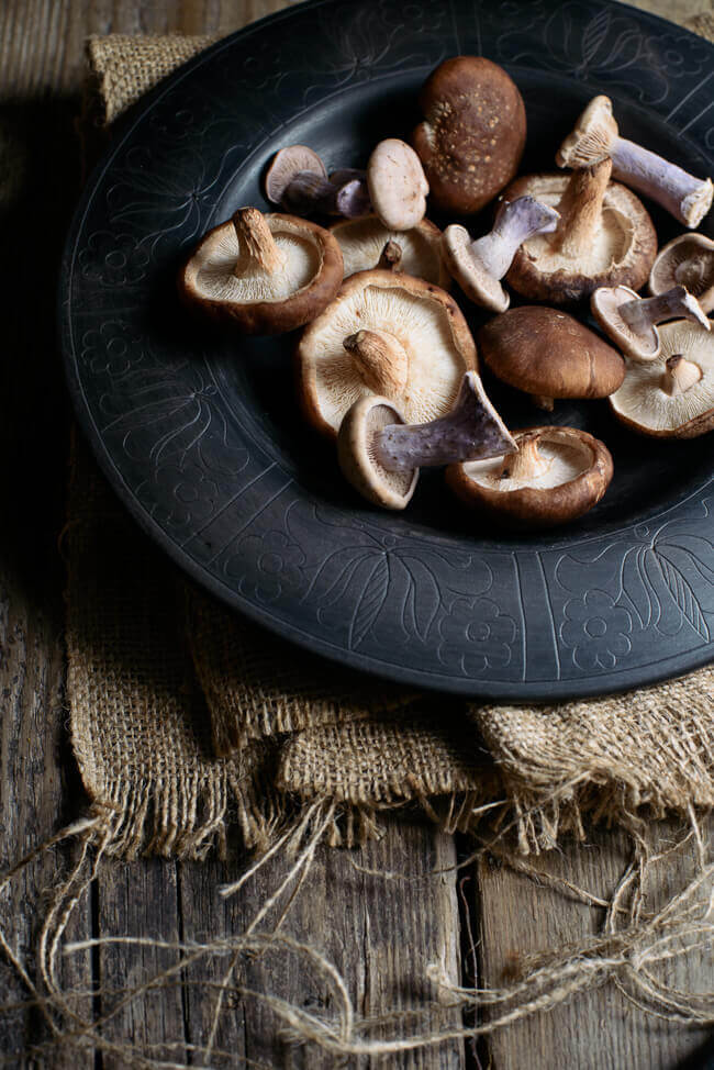 A selection of wild mushrooms in a black plate