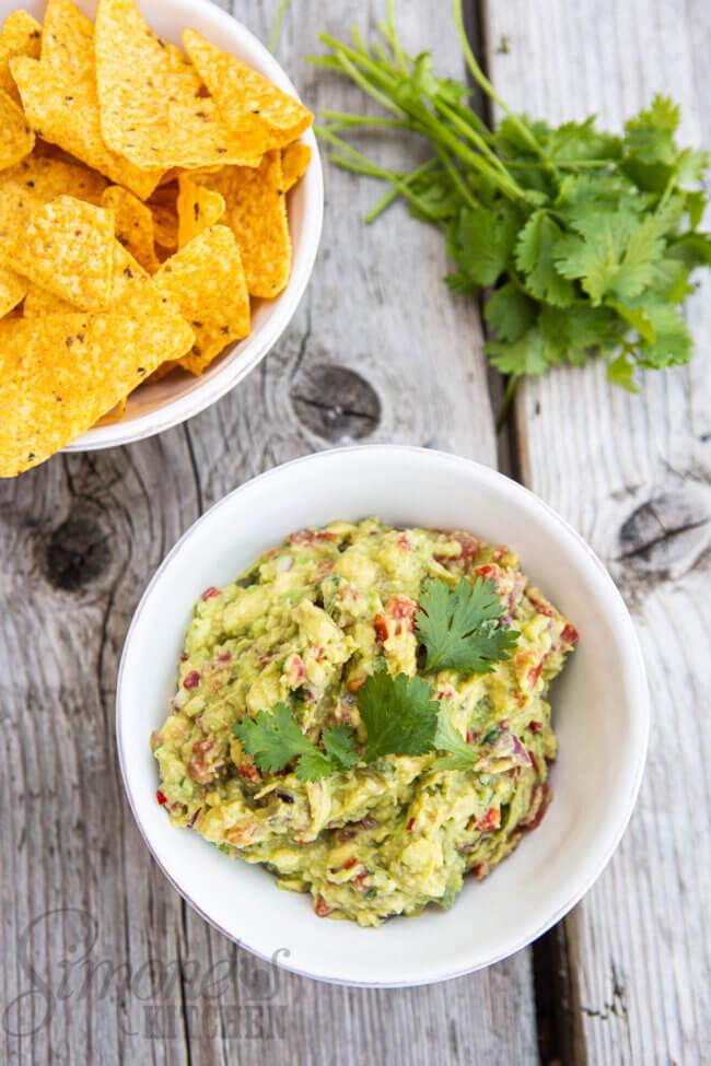 Van bovenaf bakje met guacamole en tortillachips