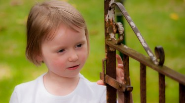 Emma examines the gate in Nanny's garden