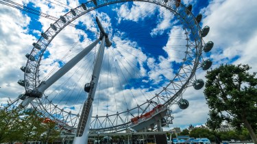 The London Eye against a blue sky with clouds