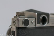 Miranda Automex III 35mm SLR camera showing battery, viewfinder release lever and sync socket