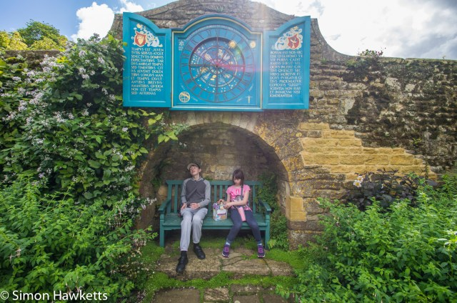 Two children sitting on a seat under an astronomical clock at Snowshill Manor