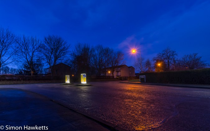 Early morning picture of 'keep left' signs against a dark blue sky