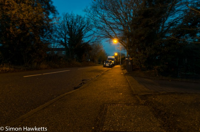 Early morning picture of a car and van under a street light