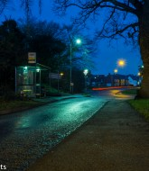 Bus stop in the early morning with the street lights reflecting off the wet road