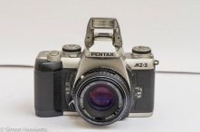Front view of Pentax MZ-3 with manual focus SMC Pentax-M 50mm f/2 lens and flash up