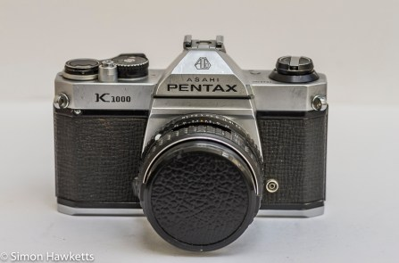 Front view of the Pentax K1000 35mm camera with lens cap on