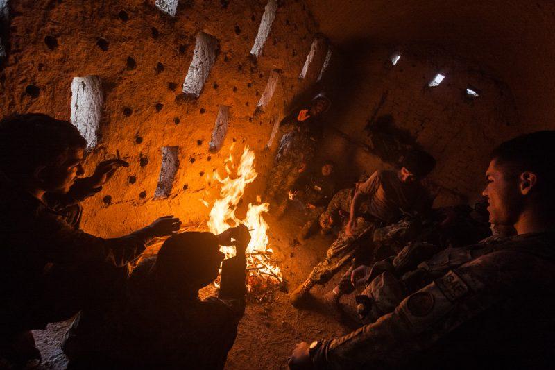 Militäroperation in Kandahar: Amerikanische und afghanische Soldaten wärmen sich in einem verlassenen Bauernhaus an einem Feuer. (c) Simon Klingert