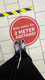 """Red dots every 2 meters leading to the cash register """"Please keep 2 Meters distance!"""""""