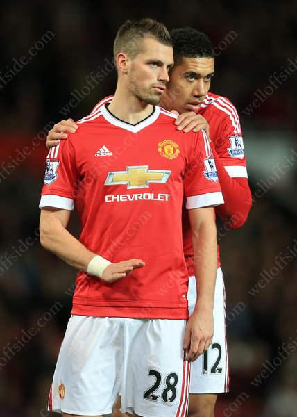 Chris Smalling of Man Utd (R)whispers to teammate Morgan Schneiderlin