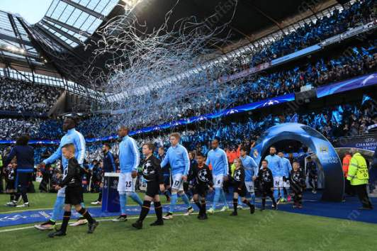 The two teams walk out onto the pitch as ticker tape goes off behind them