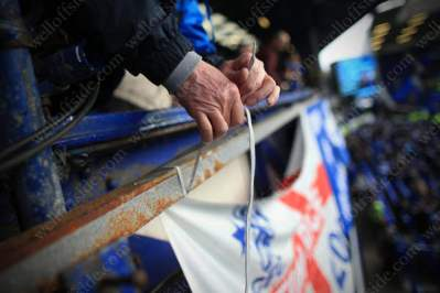 Fans' hands help tie a banner to the stand before the match